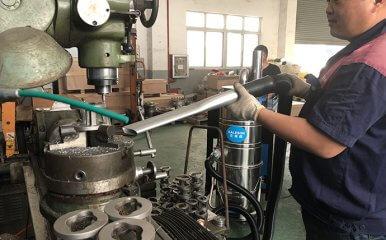工人正在用工业吸尘器收集打磨金属屑